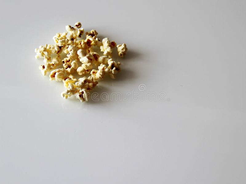 Popcorn lade ut på en vit exponeringsglastabell arkivbild