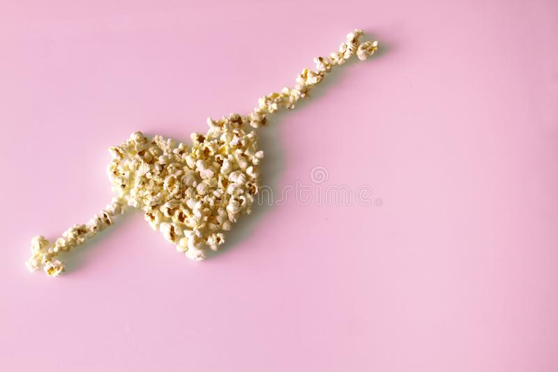 Popcorn laid out in the shape of a heart and arrows, on a pink background royalty free stock image