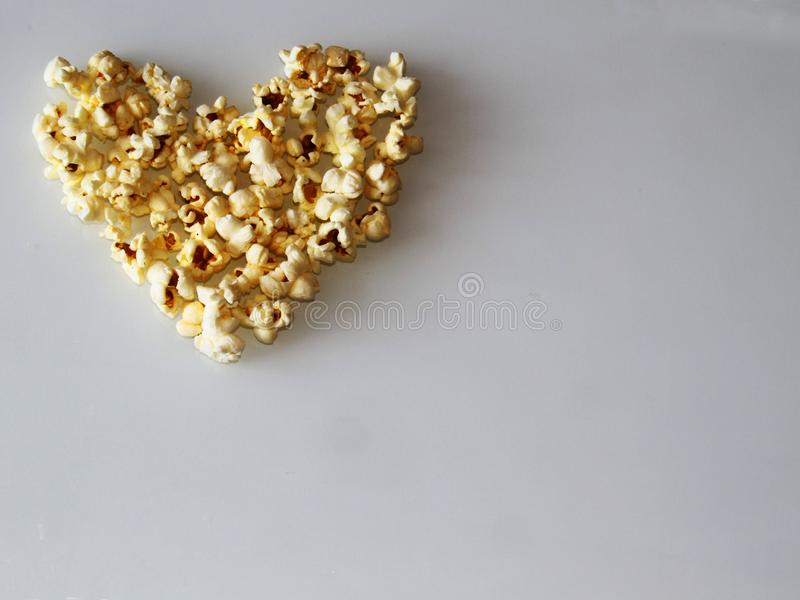 Popcorn laid out in the shape of a heart on a white background royalty free stock photos