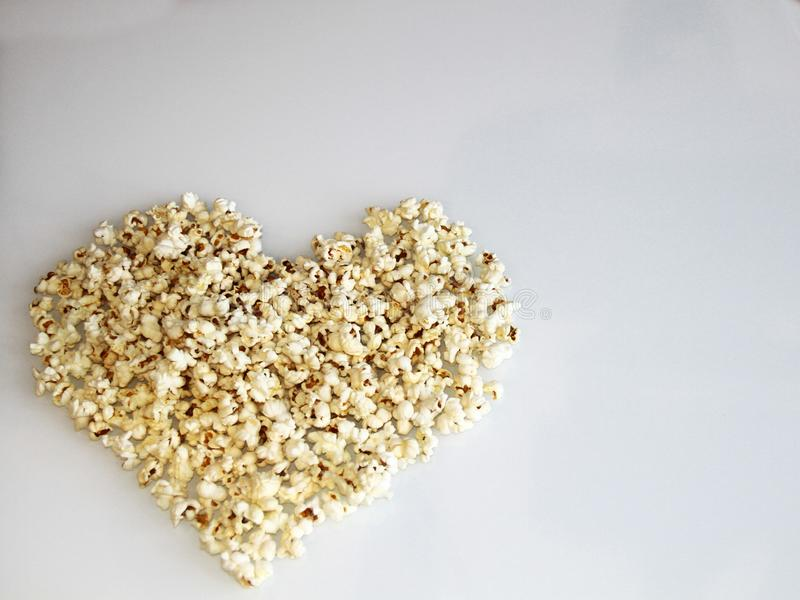 Popcorn laid out in the shape of a heart on a white background stock photos