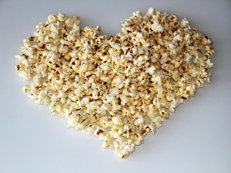 Popcorn laid out in the shape of a heart on a white background stock image