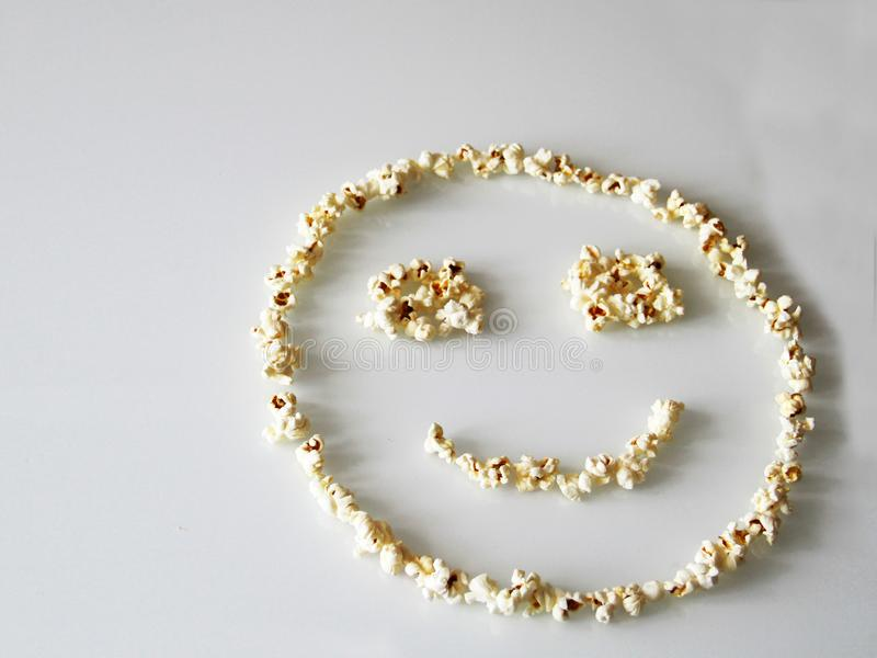 Popcorn laid out in the shape of a smiley, on a white background stock image