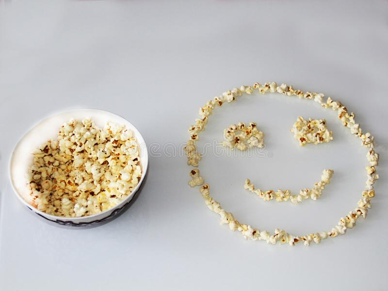 Popcorn laid out in the shape of a smiley, on a white background stock photo