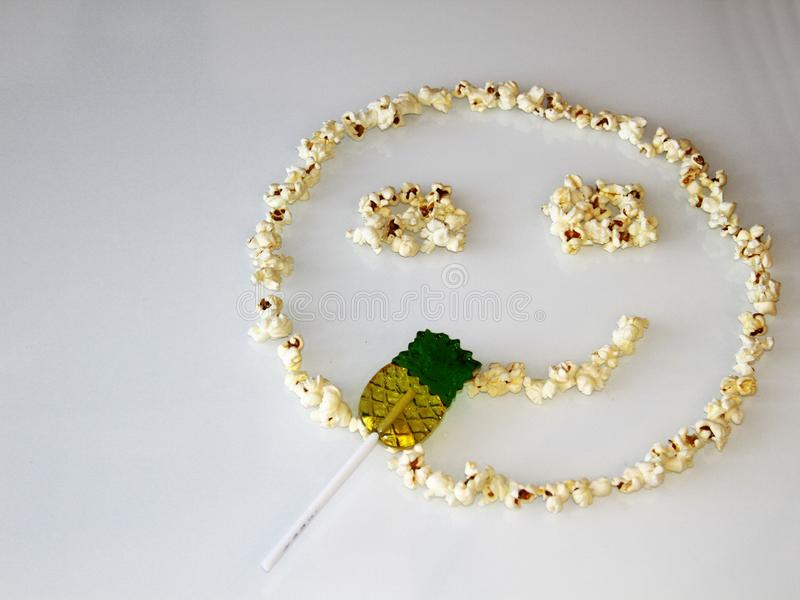 Popcorn laid out in the shape of a smiley, on a white background royalty free stock image