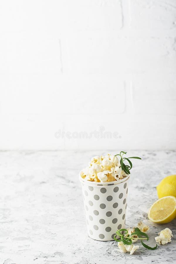 Popcorn met citroen en rozemarijn op een witte bakstenen muurachtergrond in een document kop met een patroon van erwten Selectiev royalty-vrije stock foto's