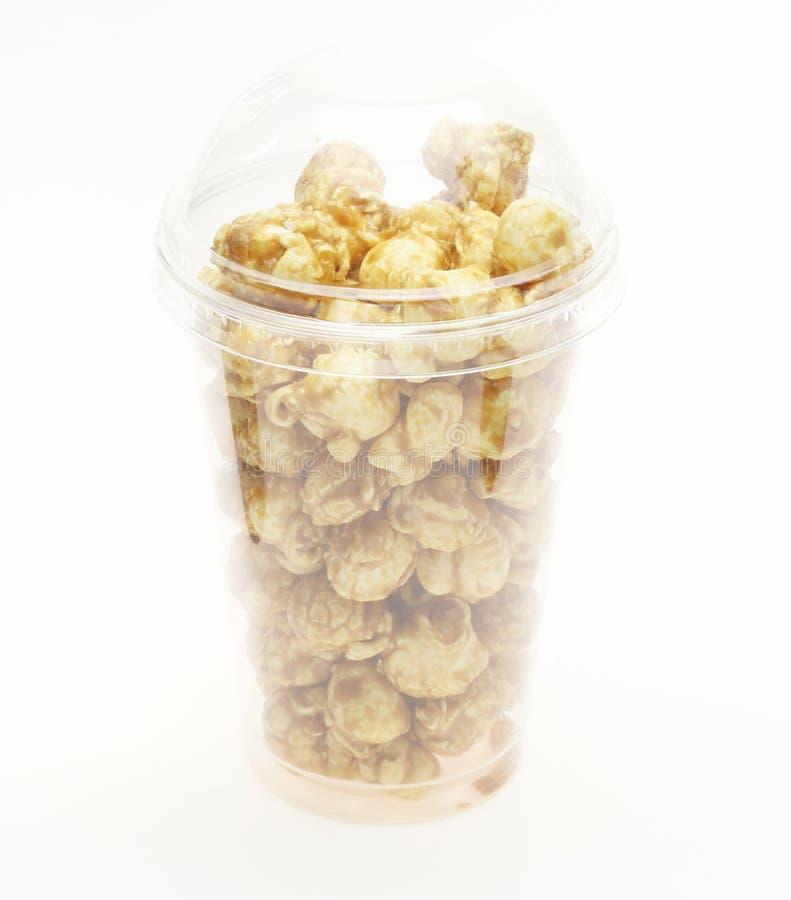 Popcorn met karamelstroop wordt gecombineerd in een plastic kop die stock fotografie