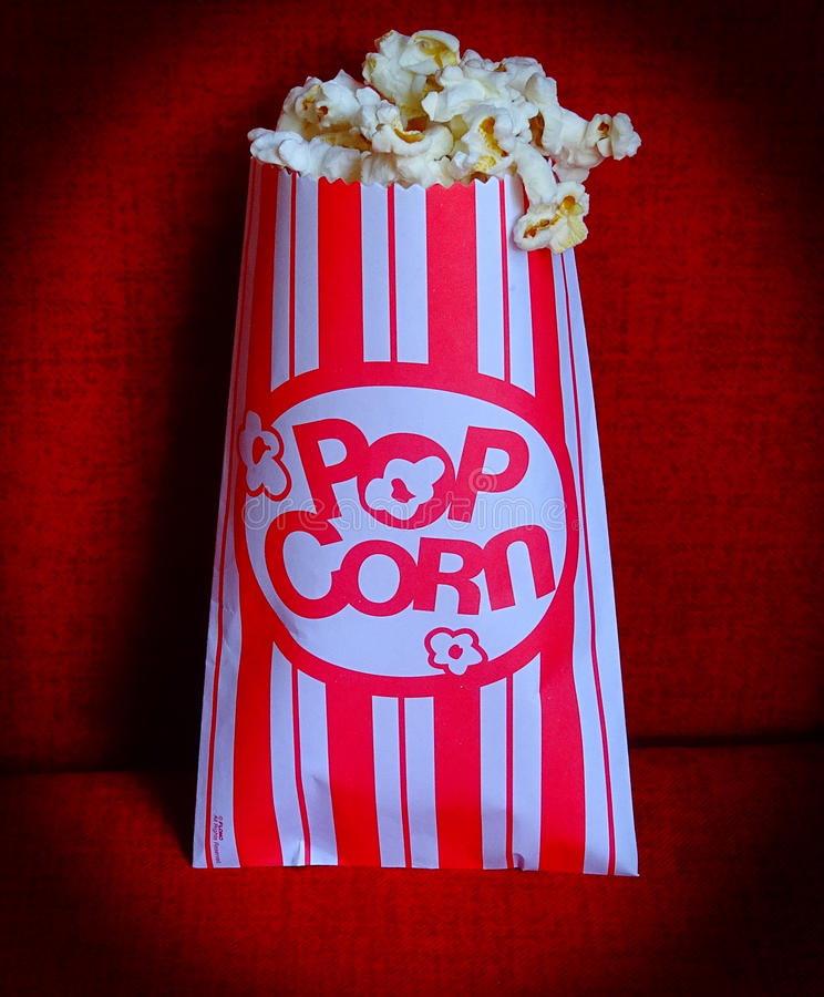 Popcorn-Movie. Bag of Popcorn in movie theater seat. Red and white striped bag. Family movie night royalty free stock images