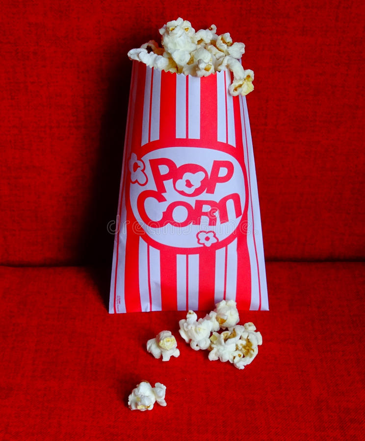 Popcorn-Movie. Bag of Popcorn in movie theater seat. Red and white striped bag. Family movie night stock photos