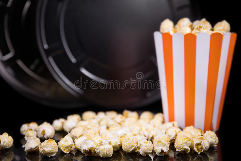 Popcorn and a movie role in front of black, concept cinema and t. Popcorn and a movie role in front of black background, concept cinema and theater stock image