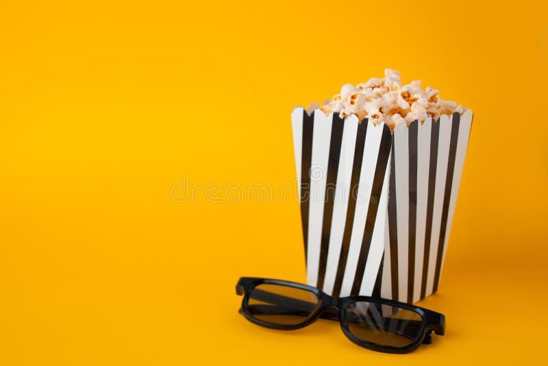 Popcorn nel supporto del sacco di carta sui vetri gialli del nero 3d del fnd di vista superiore del fondo immagini stock