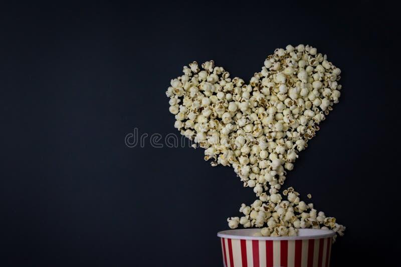 Popcorn nella forma del cuore su fondo nero Amante di film fotografia stock libera da diritti