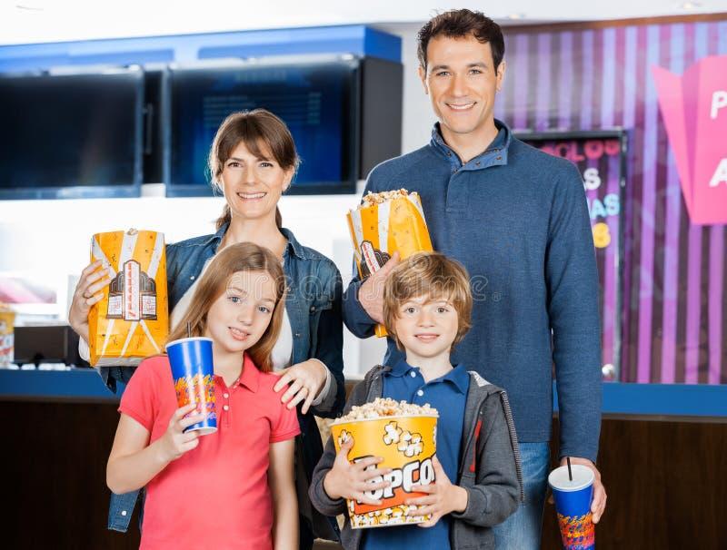 Popcorn och drinkar för familj hållande på bion arkivfoto