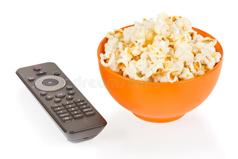 Popcorn in a orange bowl and remote control stock photography