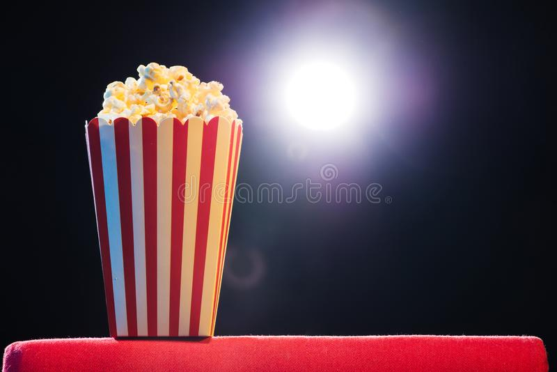 Popcorn over cinema light background, movie concept stock photos