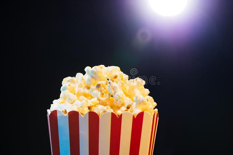 Popcorn over cinema light background, movie concept royalty free stock image