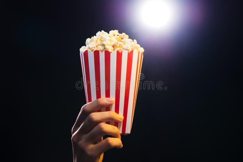 Popcorn over cinema light background, movie concept royalty free stock photography