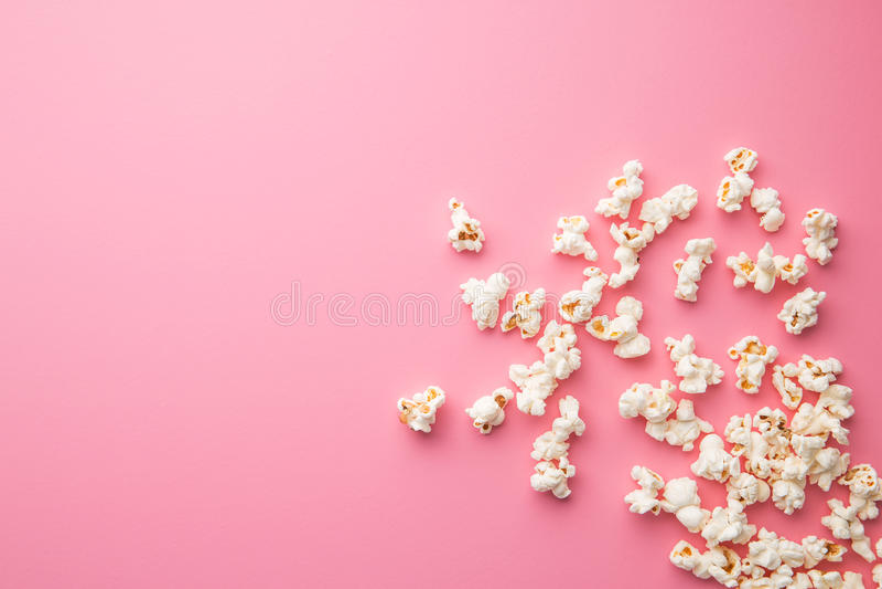 Popcorn på rosa bakgrund arkivbilder