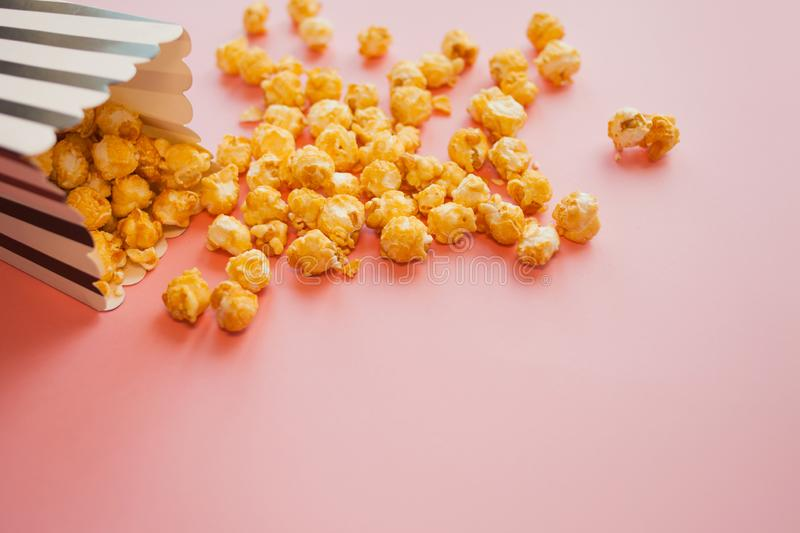 Popcorn in paper bag scattered on pink background top view royalty free stock photography