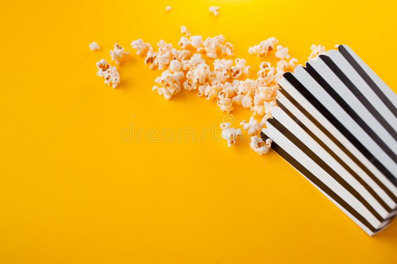 Popcorn in paper bag scattered on yellow background top view royalty free stock photography