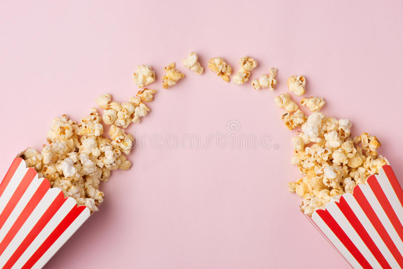 Popcorn in red and white cardboard box on the pink background. stock image