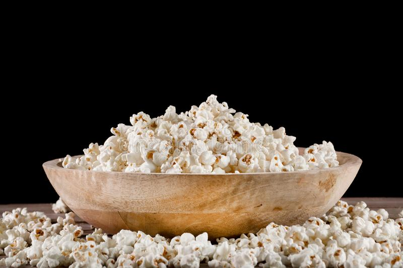 Popcorn in retro wooden bowl and spilled on wooden desk. Piles popcorn in retro wooden bowl and spilled on wooden desk and black background. Food concept. Close royalty free stock photo