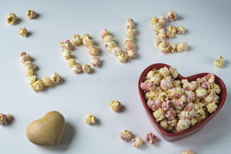 """Popcorn rosa bianco in ciotola di forma del cuore e """"amore """"scritto con popcorn immagini stock libere da diritti"""