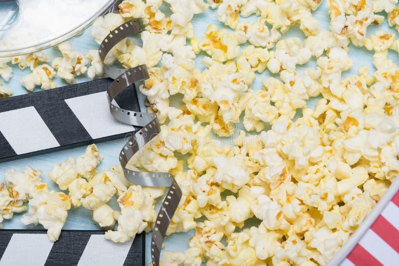 Popcorn, rot-weiße Papierschale und alter Videobandhintergrund stockfotografie