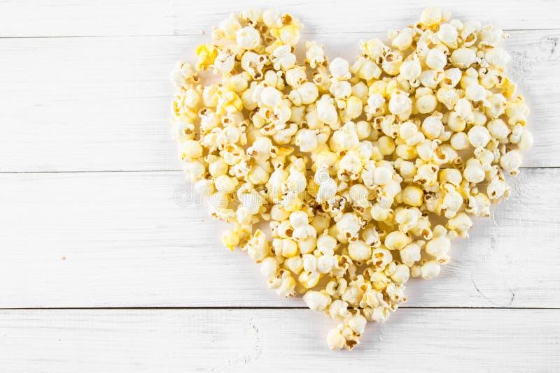 Popcorn salato sotto forma di cuore su una tavola bianca Vista superiore fotografia stock