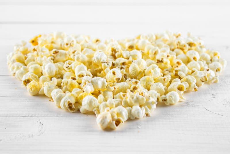 Popcorn salato sotto forma di cuore su una tavola bianca Vista superiore fotografie stock