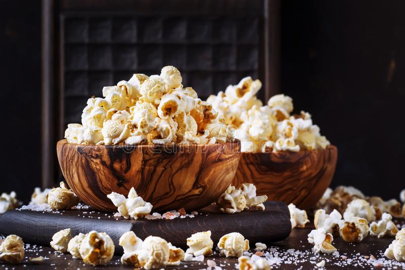 Popcorn salato in una ciotola di legno, alimento non sano, fondo di legno scuro del tavolo da cucina, fuoco selettivo immagini stock