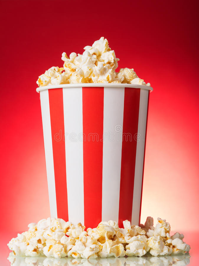 Popcorn salato in una grande scatola a strisce su rosso luminoso fotografia stock libera da diritti