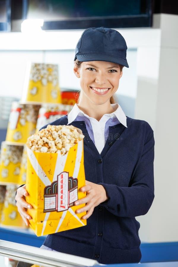 Popcorn sicuro della tenuta del lavoratore al cinema fotografia stock