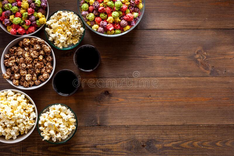 Popcorn and soda - cinema snacks - on wooden table from above space for text royalty free stock photo