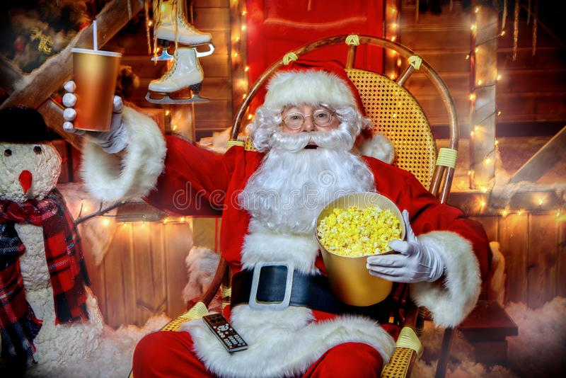 Popcorn and soda. Santa Claus sitting on his armchair eating popcorn, drinking soda and watching a Christmas movie. Entertainment and cinema concept. Merry royalty free stock photos