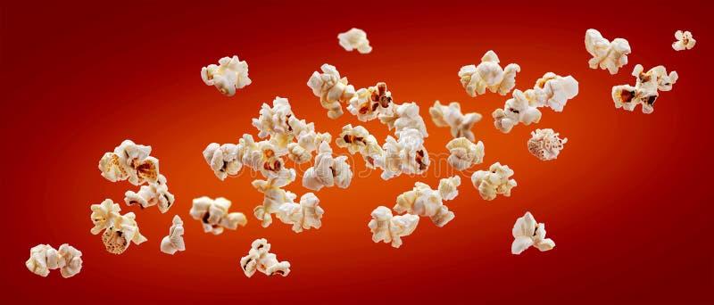 Popcorn som isoleras på röd bakgrund Falla eller flyga popcorn Närbild arkivbild
