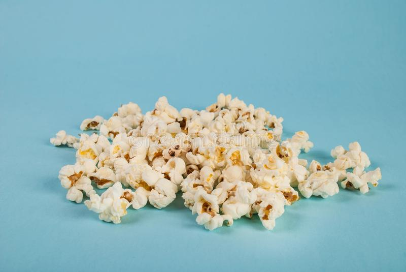 Popcorn spilled on blue background. Food concept and idea image. Close up royalty free stock photo
