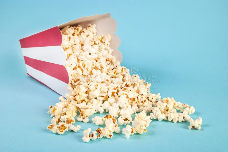 Popcorn spilled on blue background. Red and white Box of popcorn on blue background spilled and free space for text and design. Movie and Food concept. Studio royalty free stock photos
