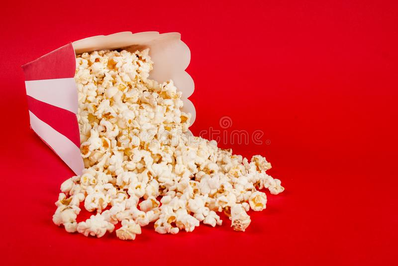 Popcorn spilled on red background. And space for text and design. Movie and Food concept. Studio shoot stock photo