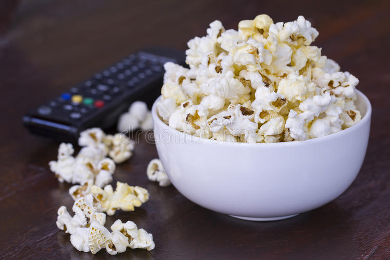 Popcorn and TV Remote Controller. Popcorn in a white bowl with a TV remote controller stock images