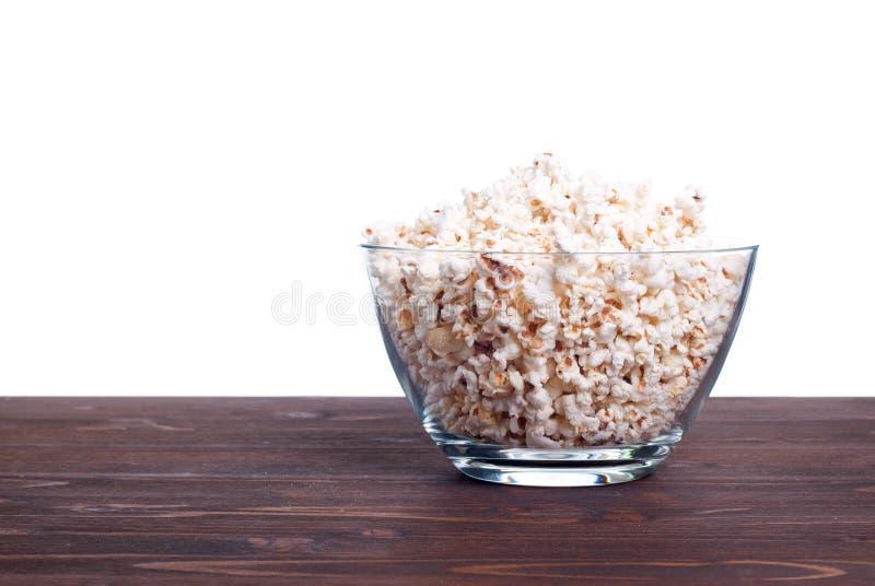 Popcorn in un vaso sulla tavola isolata su fondo bianco immagini stock libere da diritti