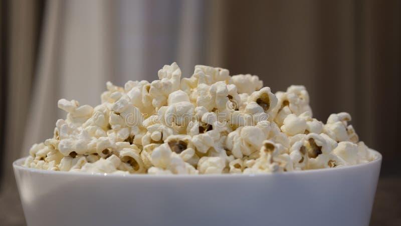 Popcorn in una ciotola bianca davanti a fondo vago fotografie stock