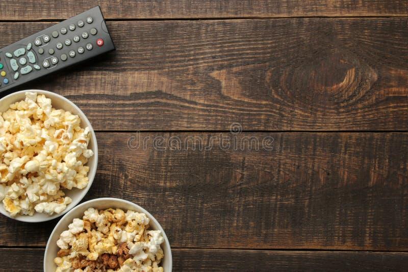 Popcorn und Fernsehen entfernt auf einem braunen hölzernen Hintergrund Konzept von aufpassenden Filmen zu Hause Draufsicht mit Ra lizenzfreies stockfoto
