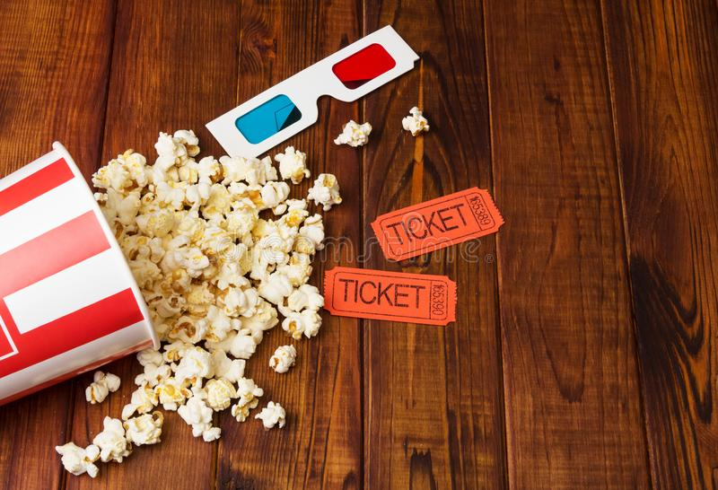 Popcorn was scattered out of the box, 3D glasses and movie tickets on dark wood. stock photography