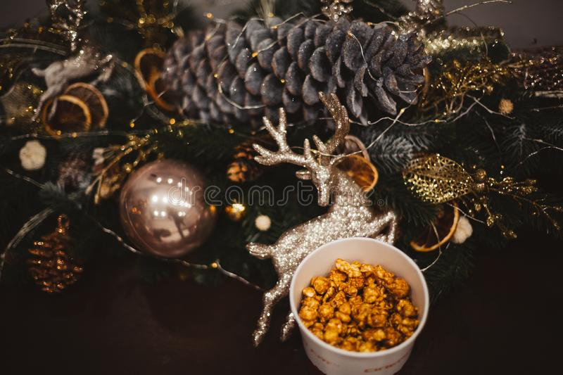 Popcorn in a wooden plate on the background of Christmas trees and Christmas decorations, New Year offer, selective focus royalty free stock image
