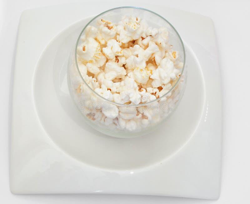 Popcorns bianchi sulla zolla bianca su priorità bassa bianca fotografia stock libera da diritti