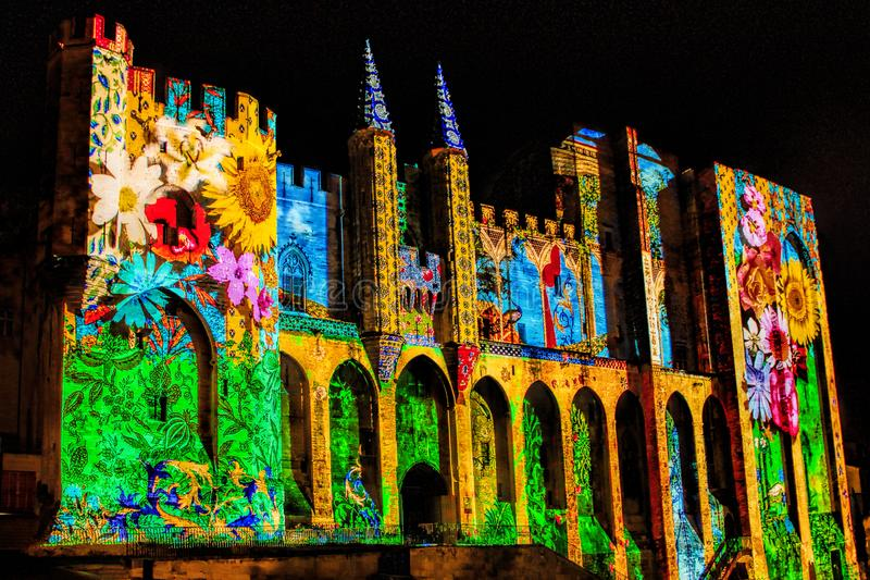 Popes` Palace in Avignon, France by night, laser show. AVIGNON/, FRANCE - NOVEMBER 29, 2013: The walls of the Popes Palace are illuminated during the light royalty free stock image