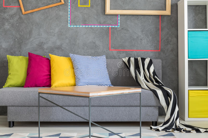 Popielata kanapa z kolorowymi poduszkami zdjęcia royalty free