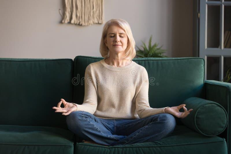 Popielata z włosami dojrzała kobieta medytuje, ćwiczy joga w domu zdjęcie royalty free