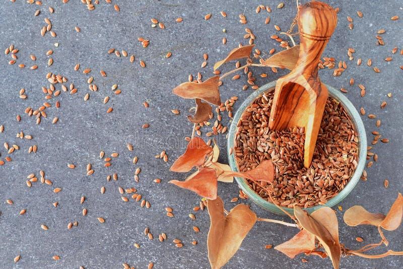 Popielaty abstrakcjonistyczny tło z szklanym pucharem z lnów ziarnami, oliwna drewniana miarka w nim, i suszymy liście zdrowe jeś fotografia stock
