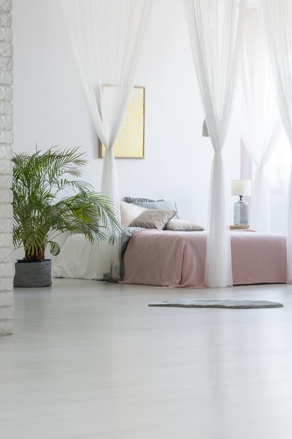 Popielaty dywanik umieszczający na podłoga w białym sypialni wnętrzu z gree obrazy stock